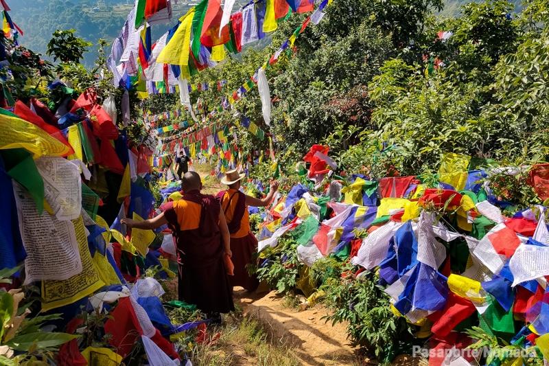 monjes budistas junto a banderas de oracion en pharping